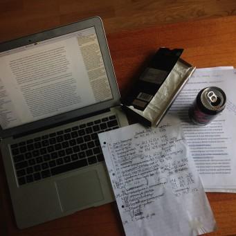 Laptop, notatark, sjokolade og brus spredd utover et bord.